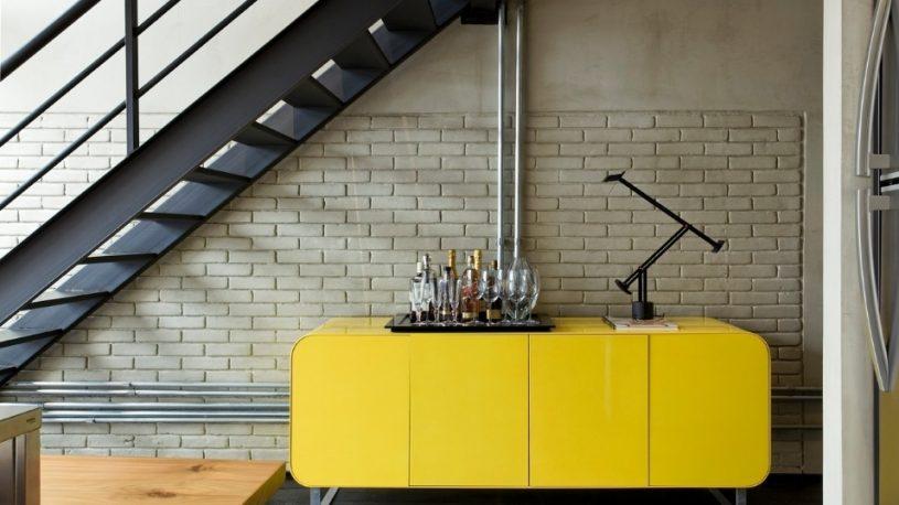 abaixo-da-escada-o-aparador-de-madeira-laqueada-de-amarelo-brilhante-funciona-como-bar-o-movel-foi-desenhado-pelo-arquiteto-diego-revollo-que-assina-a-reforma-do-loft-no-bairro-do-1349207823482_956x61